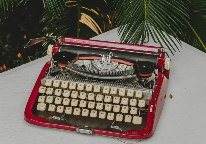A red typewriter on a white table with a fern behind it.