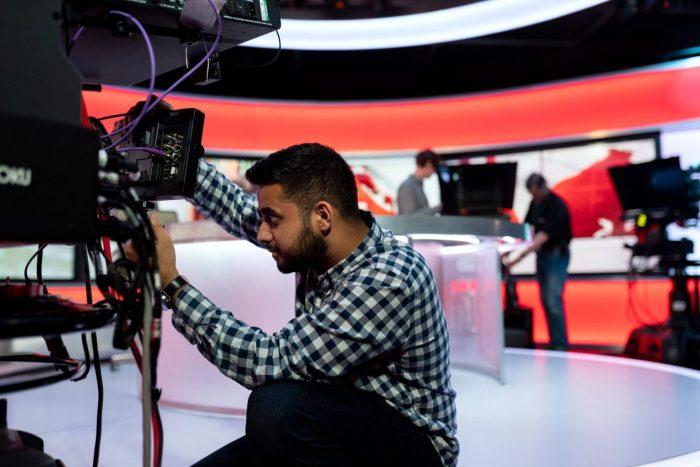 Camera operator kneeling in front of camera in BBC news studio