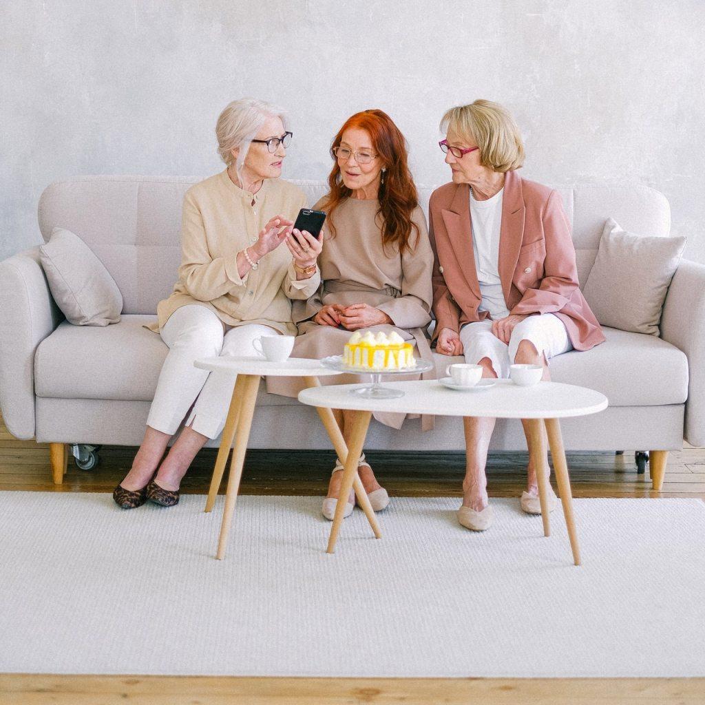 3 dames âgées assises sur un canapé gris discutant et l'une d'entre elles montre quelque chose sur son smartphone