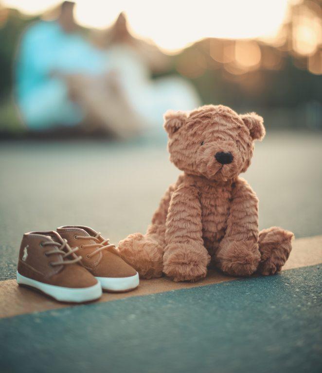Mise en scène d'une paire de chaussures à coté d'un ours en peluche