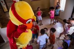 Niños juegan con Súper Pollo.