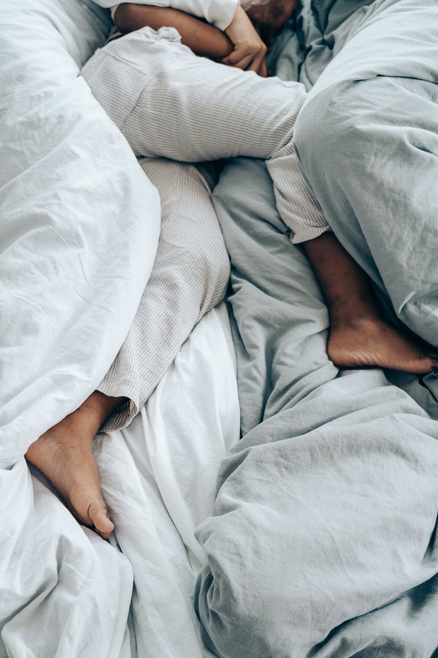 crop anonymous person lying in bed