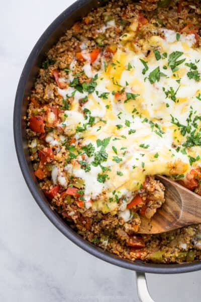 easy one pot quinoa stuffed pepper recipe in a skillet topped with cheese