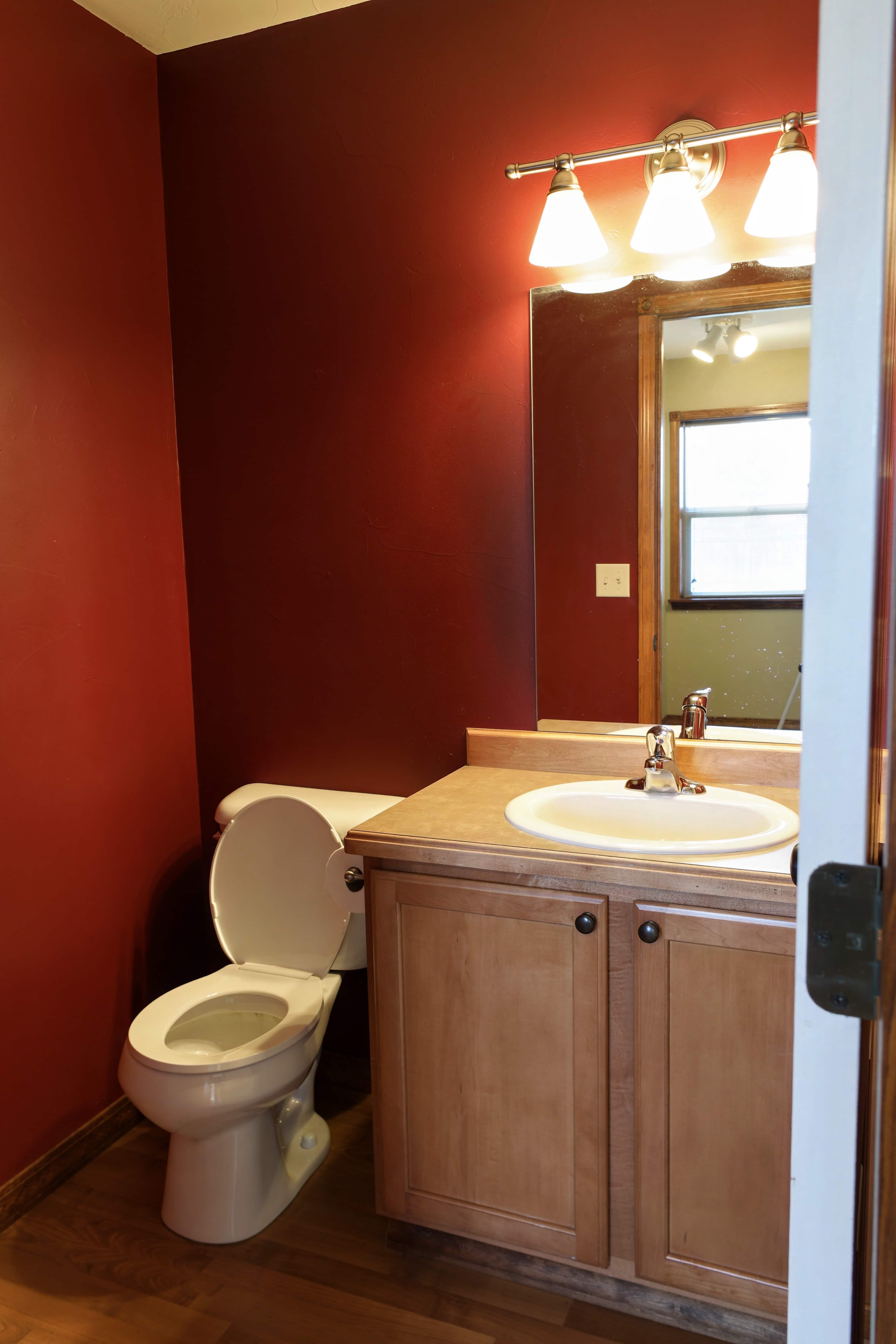 half bathroom with red walls and builder grade vanity