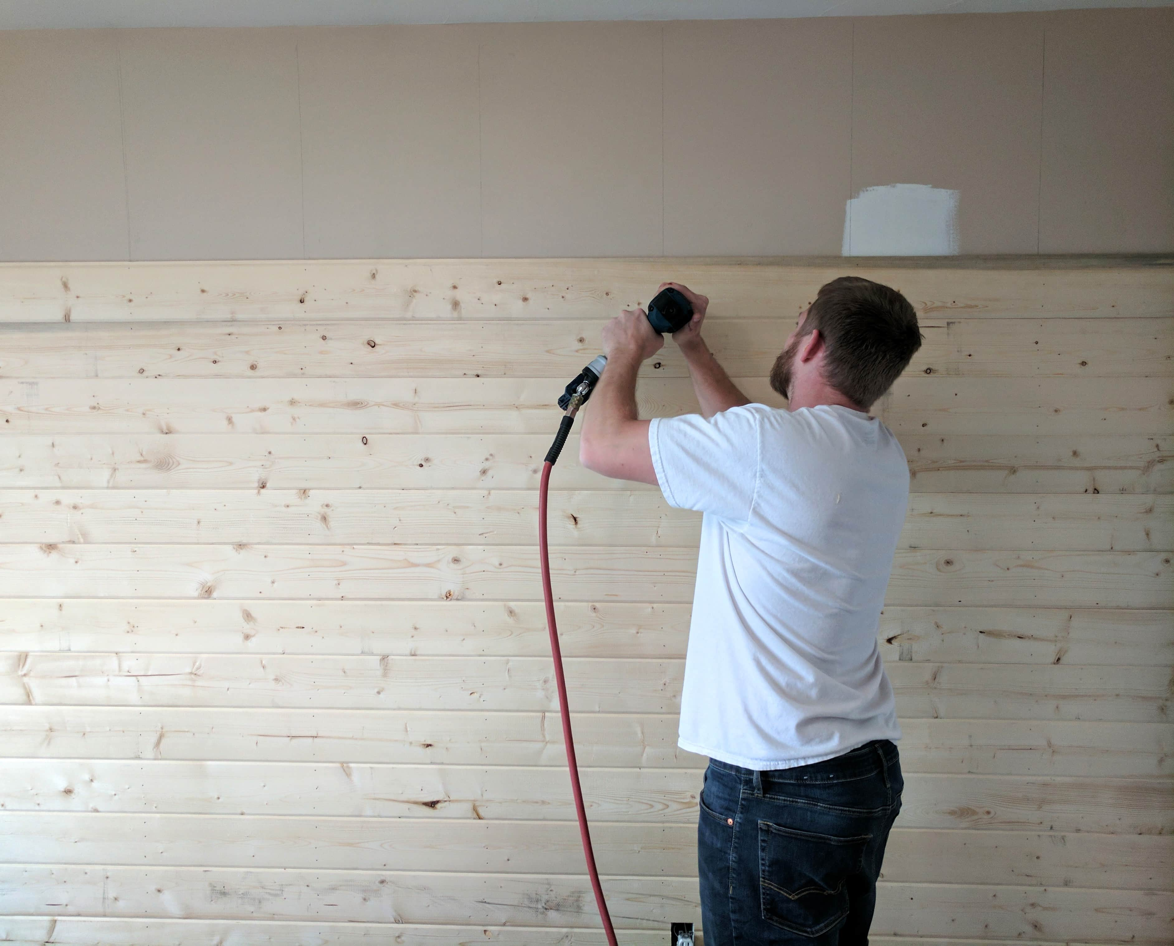 A man using a nail gun on a DIY wood plank accent wall