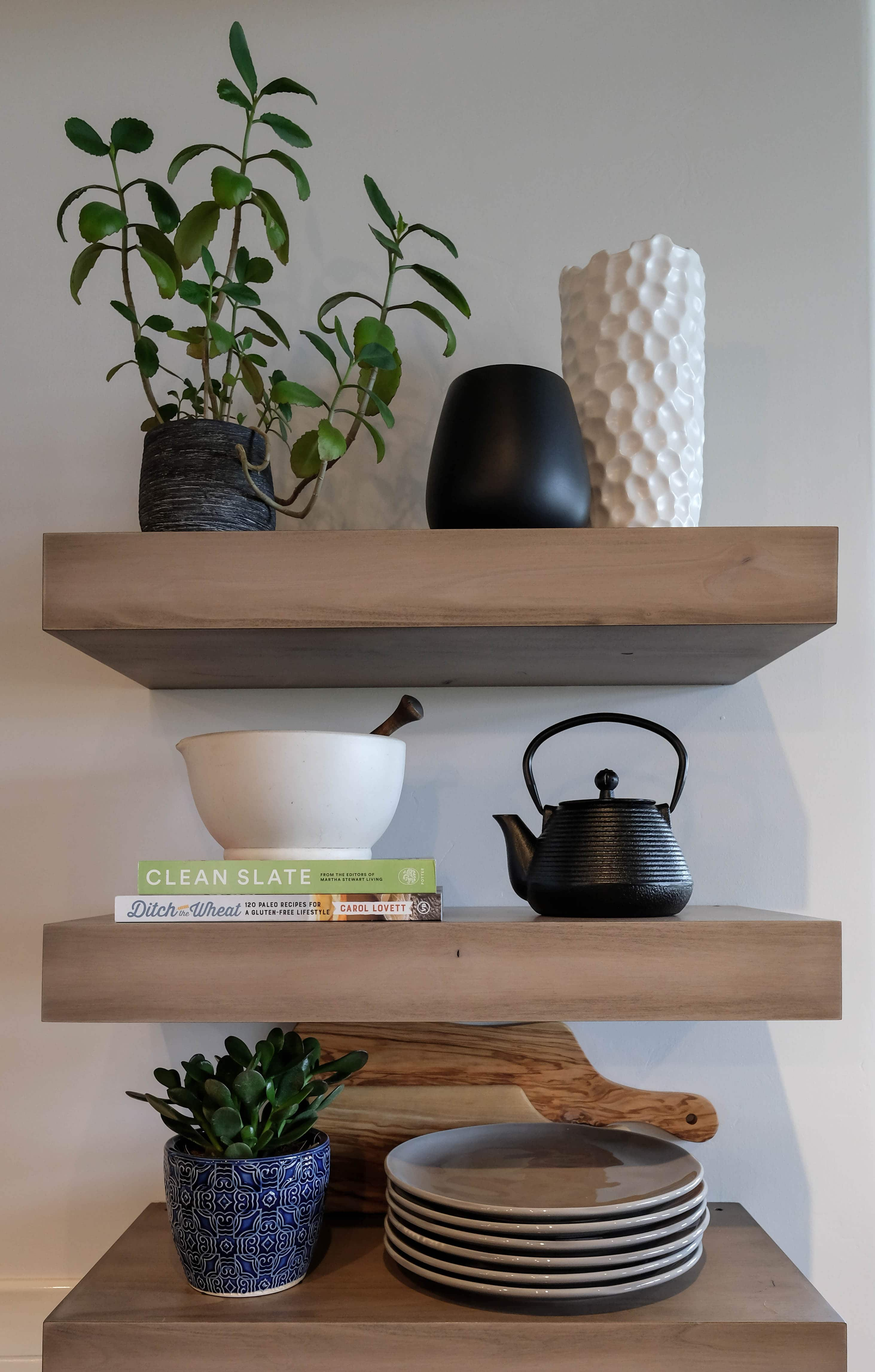 Parade of Homes styled shelf with books, plates, teapot, and plants