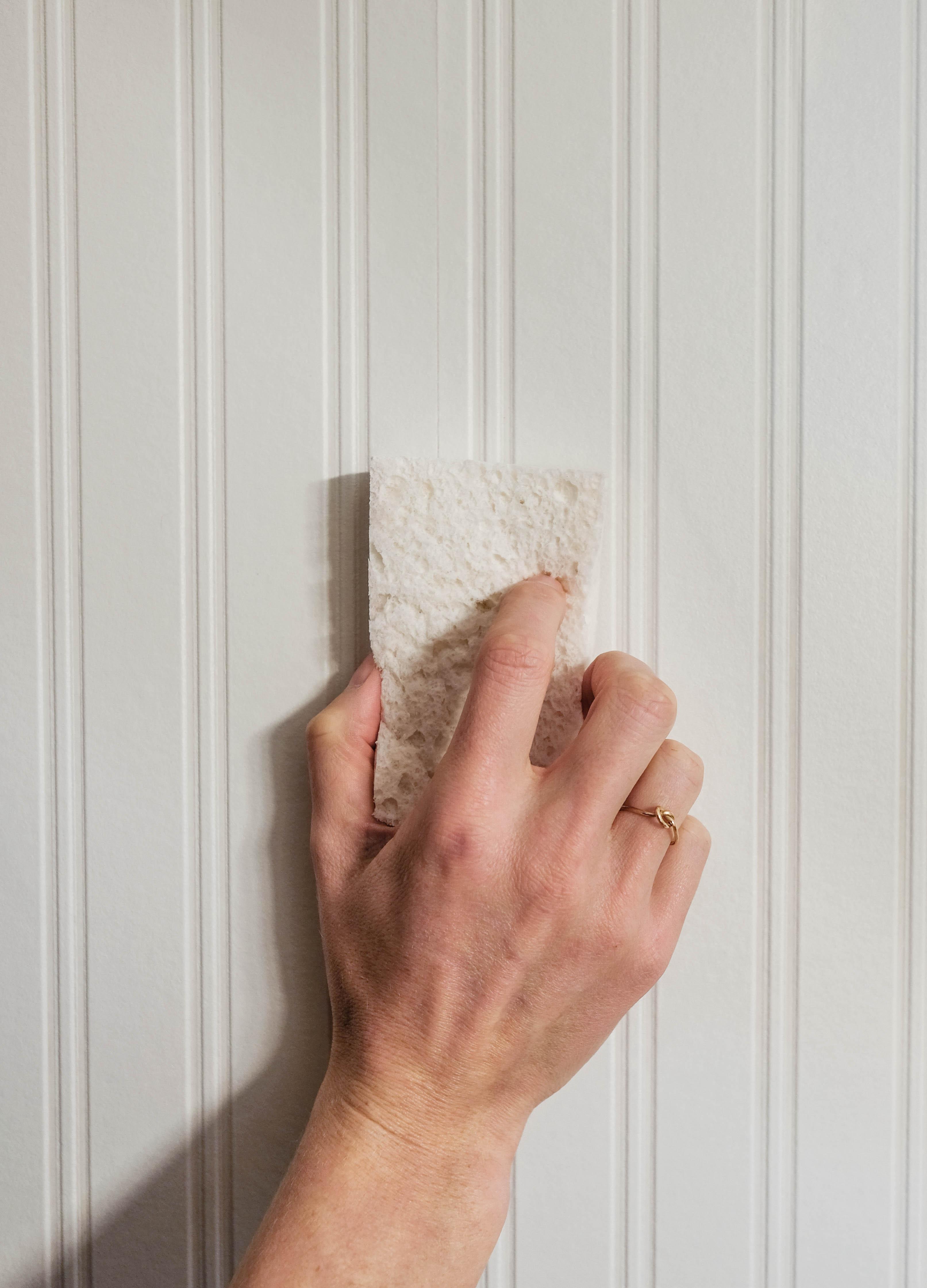 Closeup of a hand holding a sponge against beadboard wallpaper