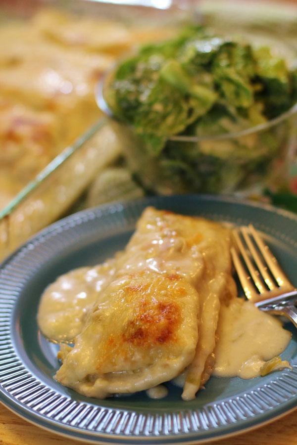 Creamy White Chicken Enchiladas on plate with fork