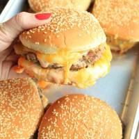 Juicy, saucy, and gooey cheeseburgers ready to serve to a crowd.