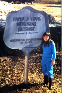 Shelby Cook standing by her Great Grandfather, David Jackson Cook's memorial plaque over 10 years ago.