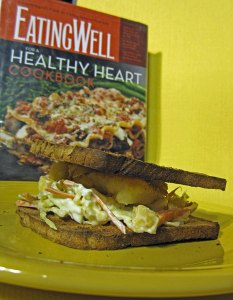 Photo of crispy fish sandwich with pineapple slaw and the book, Eating Well for a Healthy Heart Cookbook