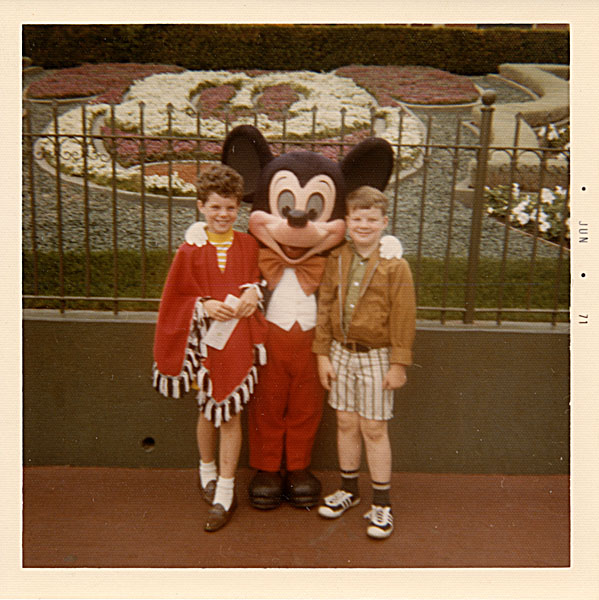 Two children standing with Mickey Mouse at Disney Land, 1971