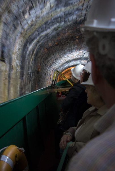 Tunnel with boat and tourists in hard hats