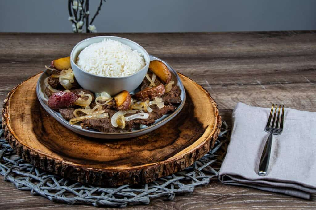 Philippine Beef Steak with potatoes and onions on a plate with a bowl of steamed rice on the side