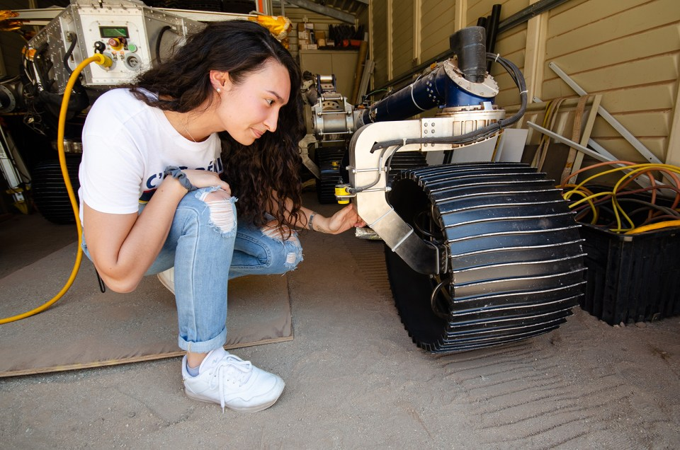 Isabel Rayas kneels down in front of the Scarecrow mars rover in a garage and places her hand on one of the front wheels