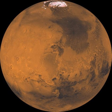 The north polar cap is visible in this projection at the top of the image from NASA's Viking Orbiter 1, the great equatorial canyon system (Valles Marineris) below center, and four huge Tharsis volcanoes (and several smaller ones) at left.