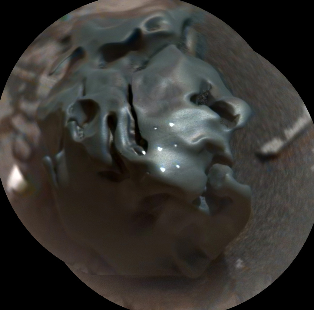 The dark, golf-ball-size object in this composite, colorized view from the Chemistry and Camera (ChemCam) instrument on NASA's Curiosity Mars rover shows a grid of shiny dots where ChemCam had fired laser pulses used for determining the chemical elements in the target's composition.