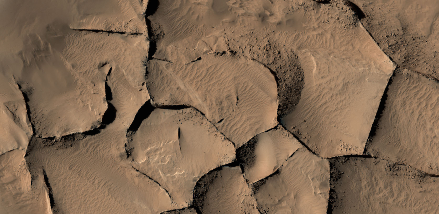 This view shows part of an area on Mars where narrow rock ridges, some as tall as a 16-story building, intersect at angles forming corners of polygons.