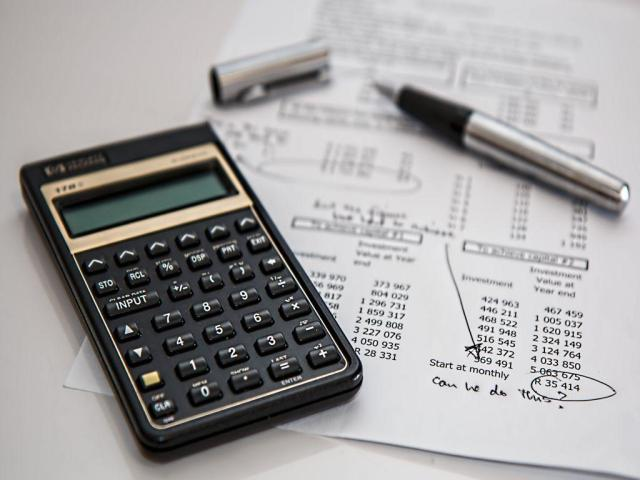 A calculator, a pen and a bill on a white surface.