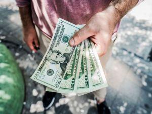 A man holding 20 dollar bills.