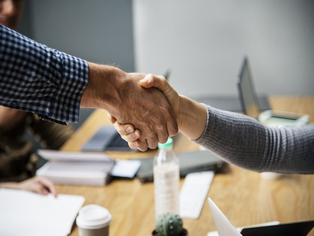 Two people shaking hands over a deal.