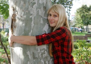 A young blonde woman in flannel hugging a tree and smiling at the camera.