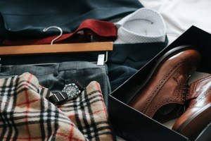 Clothes and shoes on a bed.