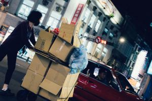 A woman wheeling around a bunch of boxes.