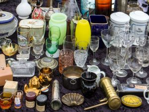A wide variety of glassware and other items at a flea market.