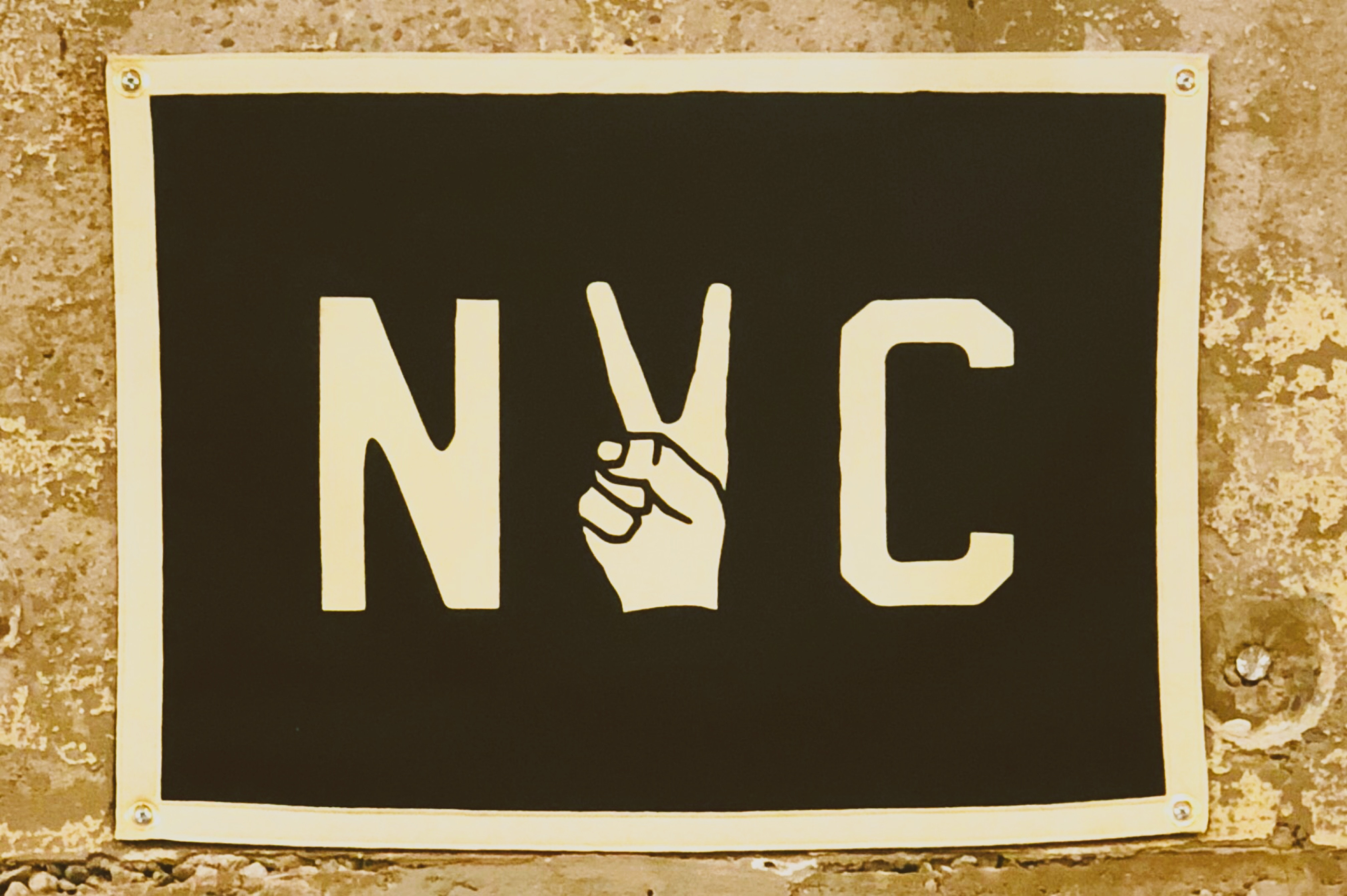 A poster saying NYC where the Y is a hand making the peace sign. If you hire movers Carroll Gardens, you'll be a part of city pride!