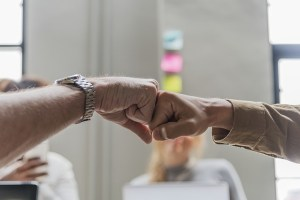 Two people fist bump.