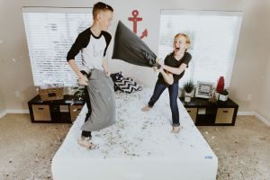 A boy and a girl having a pillow fight in a room.