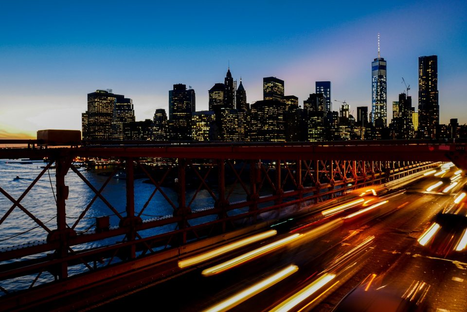A long-exposure shot of light trails on the freeway with the New York city skyline at the back - if you hire moving companies Suffolk County NY, you won't have to move frenziedly back and forth across it.