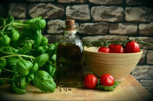 Basil, olive oil and a bowl with tomatoes on a table