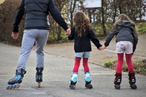 A father, roller skating with his two daughters.