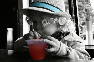 Child drinking red beverage.