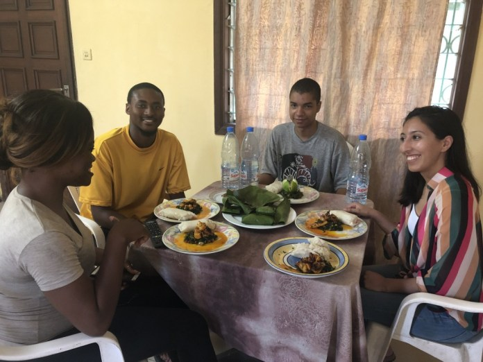 Markus Brooks, a criminal justice major at JSU, and students from the East coast, indulge in local cuisine during their stay in Cameroon,where they witnessed the Cameroon justice system in action, toured the sites and helped residents learn more about the medical center in the ares. (Photo special to JSU)