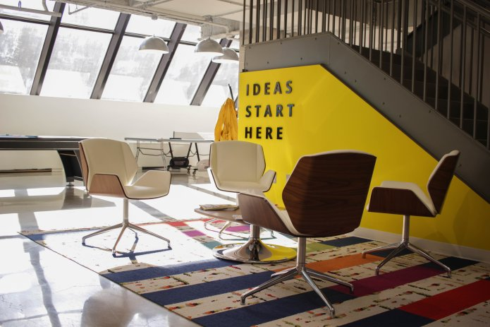 Four empty office chairs in front of a yellow staircase with the words 'ideas start here'.