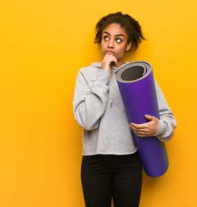 Woman in sweatshirt holding a yoga mat, with hand on chin confused.