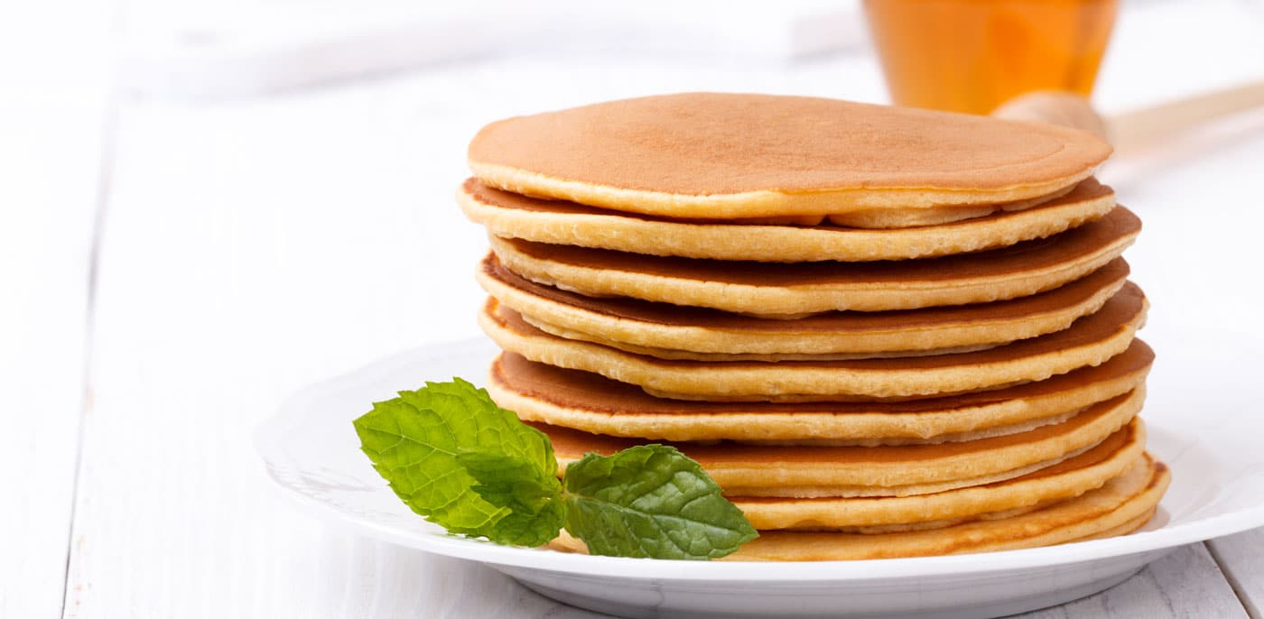 Stack of maple pancakes on a white plate with fresh mint