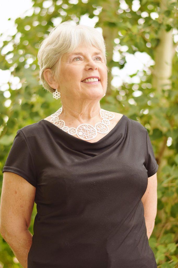 Women 60+ and her White Coruu necklace & earrings