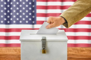 Hand placing ballot into a box.
