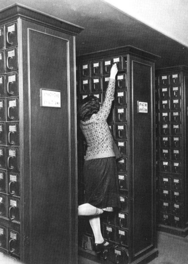 8. Bibliotecaria buscando en cajones superiores del catálogo de fichas catalográficas