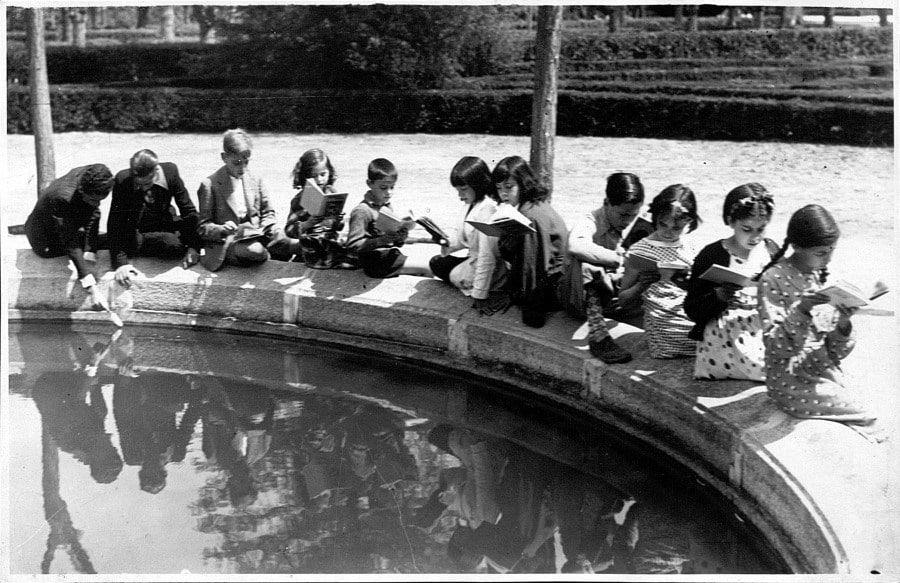 Niños leyendo en la biblioteca del parterre del Retiro