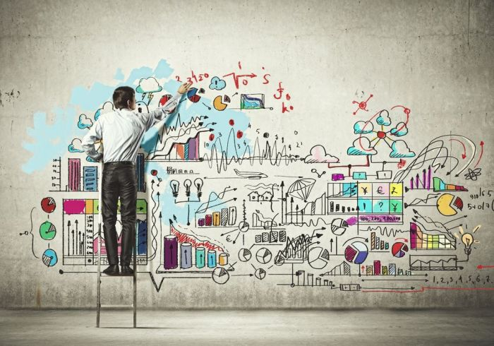 Back view of businessman drawing sketch on wall from Shutterstock