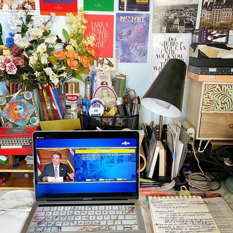 Desk with floral decor in mason jars, office supplies, and a wall with postcards over a desk with a MacBook Pro with Governor Andrew Cuomo giving his daily press briefing on the coronavirus pandemic situation in New York State.