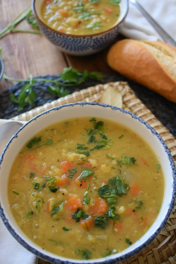 split pea and carrot soup in a bowl with soup in the background