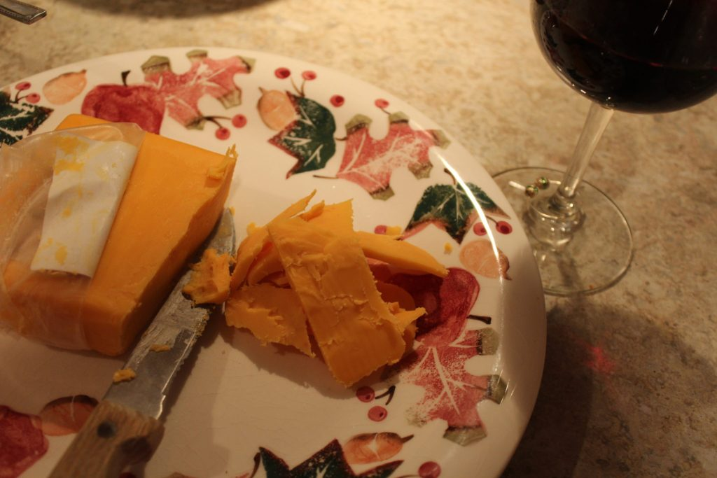 cheddar cheese slices and glass of red wine