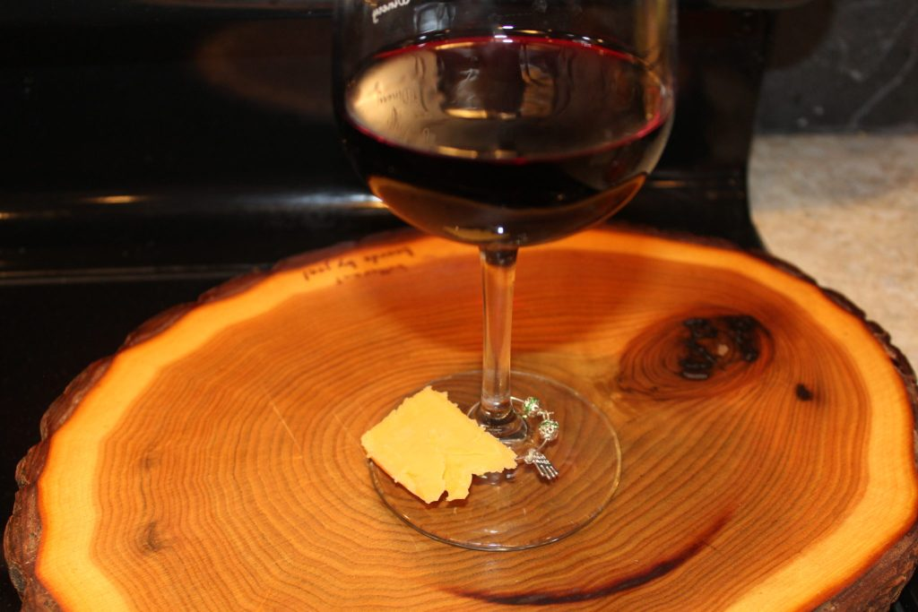 Glass of red wine with cheddar cheese chunk on stemmed wine glass base