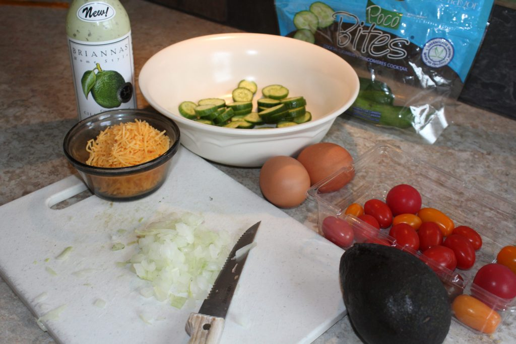 The Seven Ingredients for the salad: dressing, cucumbers, eggs, cheese, onion, tomatoes, and avocado.